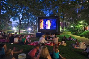 image of peopleoutdoors looking toward a large screen showing a movie