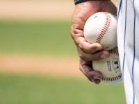 Closeup of someone wearing a baseball uniform holding two baseballs
