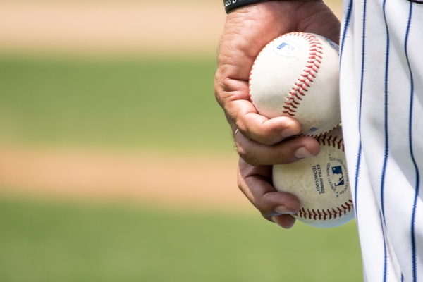 Closeup of someone wearing a baseball uniform holding two baseballs