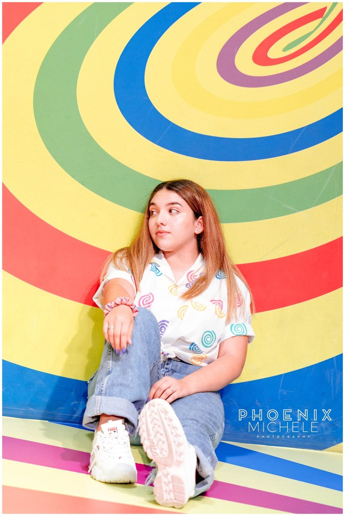 lady sitting against multi colored background