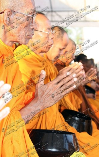 Monks accept alms from and give blessings to the red-shirts