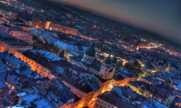 Феєричне фото центральної частини вечірнього Львова згори з кольоровою підсвіткою.