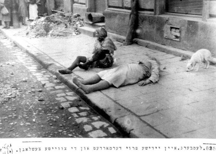 Жінка, що сидить біля мертвого тіла на вулиці Львівського гетто.