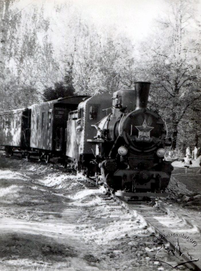 Ось в таких дерев'яних вагонах, що позаду паровоза, перевозили пасажирів в перші роки існування Дитячої залізниці. Фото 1951-1956 рр.