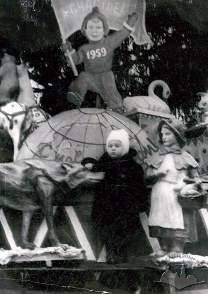 Різні казкові персонажі теж складали компанію Діду Морозу під ялинкою. Хлопчик на глобусі ніс прапор щастя з року в рік, змінюючи лиш номер року на грудях. Фото 1957 року