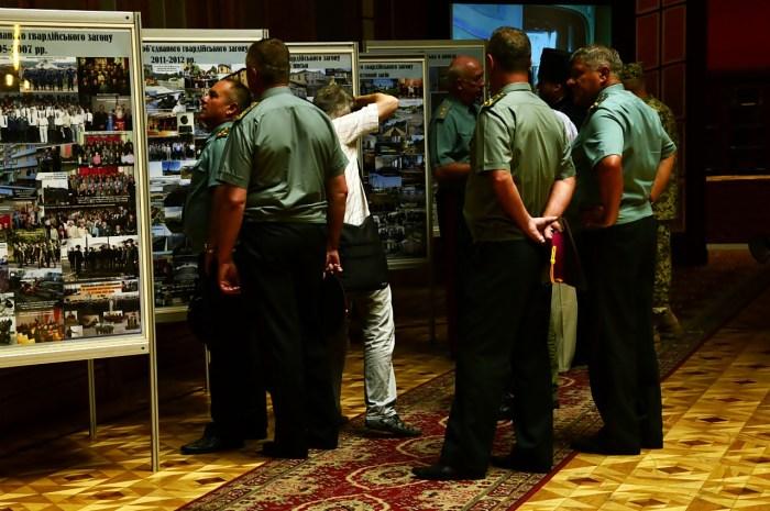 """Офіцери розглядають """"Фотолітопис 1 обєднаного гвардійського загону"""""""