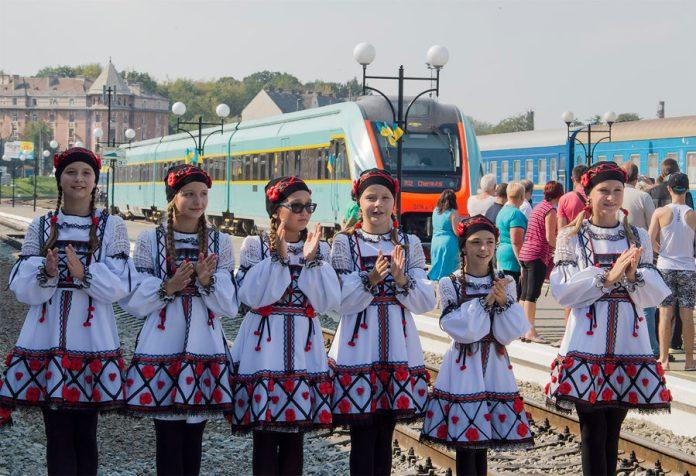"""Колектив """"Смайлики"""" на тлі дизель-потягу, який прибуває до вокзалу в Чернівцях. Фото: Ксенія Янко"""