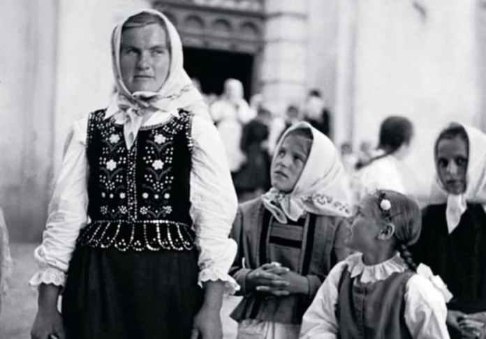 Дівчина у святковому одязі стоїть під церквою у Сокільниках (село Пустомитівського району Львівської обл.), чекаючи на приятеля. Молодша дівчинка прикрасила волосся живими квітами