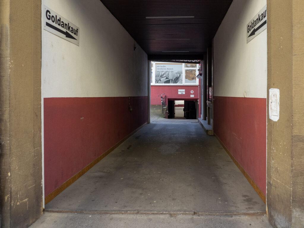 Das Bild zeigt eine längere Einfahrt die sowohl an den Seiten als auch im Hintergrund in der unteren Hälfte rotbraun und oben schmutzigweiß ist