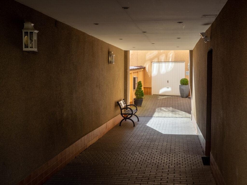 Das Bild zeigt eine im Hintergrund sonnige Einfahrt in Gelbtönen mit einer Sitzbank links