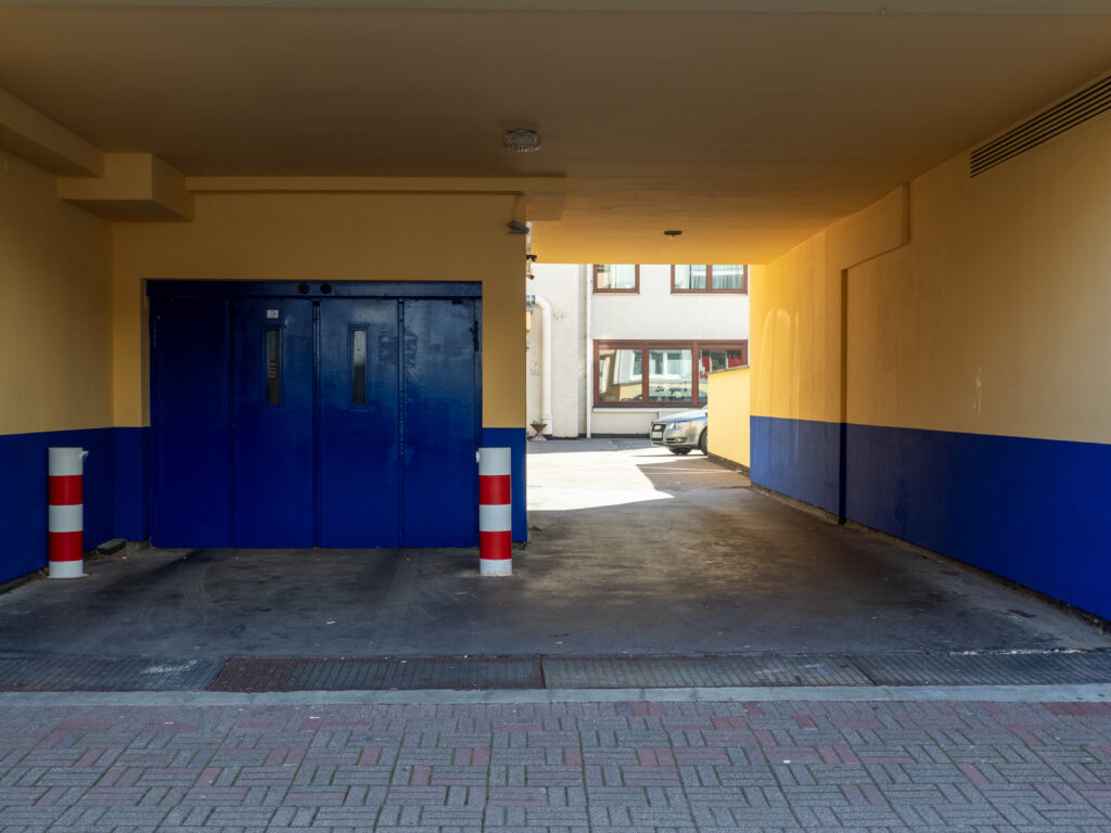 DAs Bild zeigt iene Einfahrt neben einer Blauen Garagentüre mit einem Ritweißen Pfosten in der Mitte