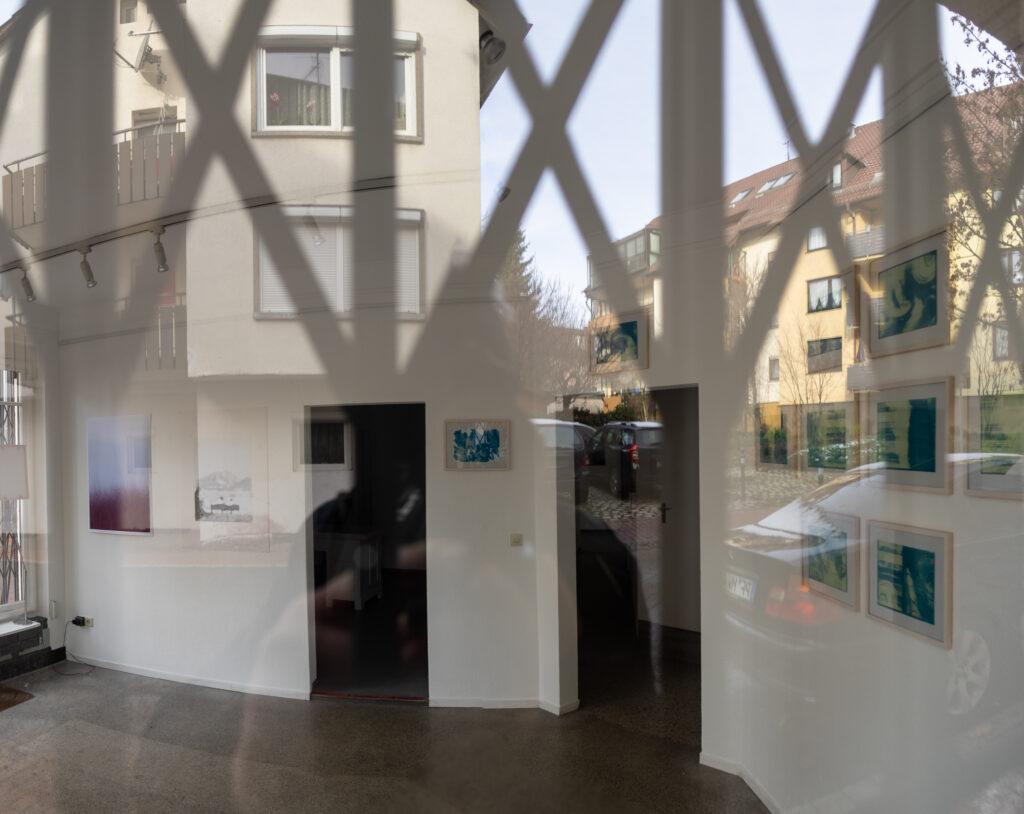 Das Bild zeigt das innere einer Galerie gesehen durch die vergitteretn Fenster. Das Gitter und die gegenüberliegende Straßenseite spiegeln sich in der Fensterscheibe vor den ausgestellten Bildern