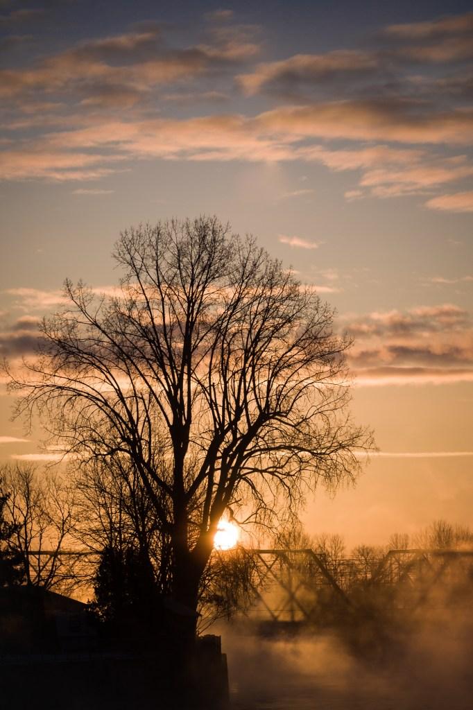 Lever de soleil au-dessus du Vieux-Pont de Terrebonne avec un arbre défolié en silhouette