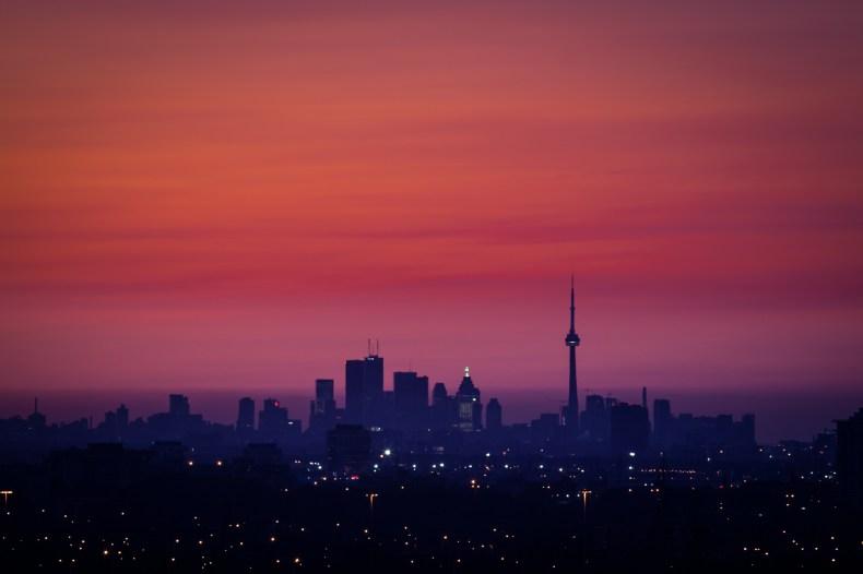 Toronto, avec la tour du CN, en silhouette avec les nuages colorés par un soleil sur le point de se lever.