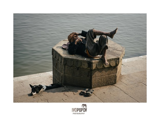 Local man sleeping next to a dog on the ghats in Varanasi.