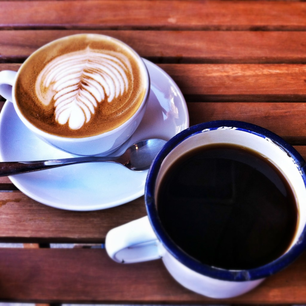 Two coffees, a flat white and a black filter coffee, on a wooden table