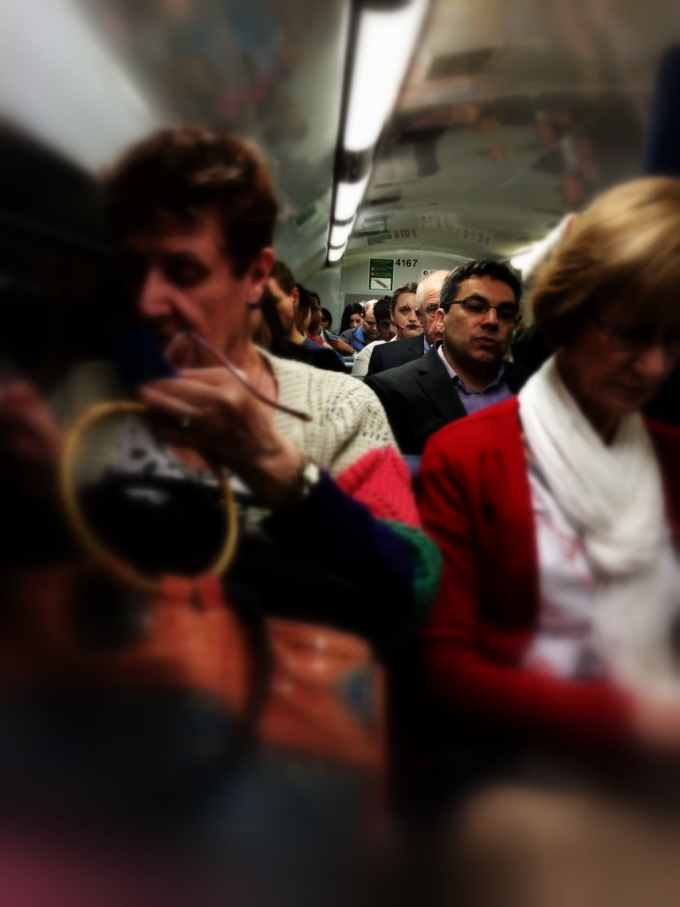 peak hour train passengers, one is made up as a zombie