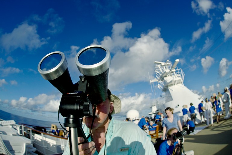 A man looks at the partial solar eclipse through binoculars and filters while at sea in Pacific Ocean.