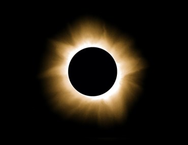 Photo of total solar eclipse with solar flares by Rick Feinberg.