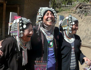 A Wilderness Travel traveler (center) laughs surrounded by two Akha hill tribe women in Burma. She is wearing their traditional headdresses and jewelry..