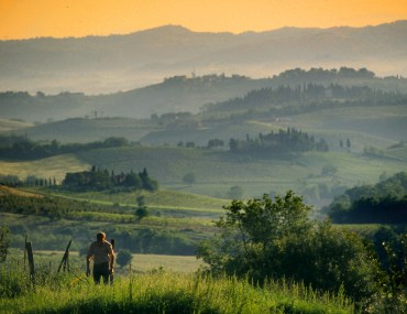 Man walking in the hills in Tuscany, Italy, at sunset.