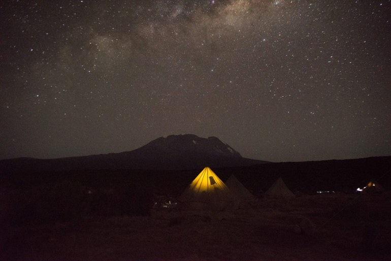 Day 2 tent lit up against the dark Kilimanjaro silhouette