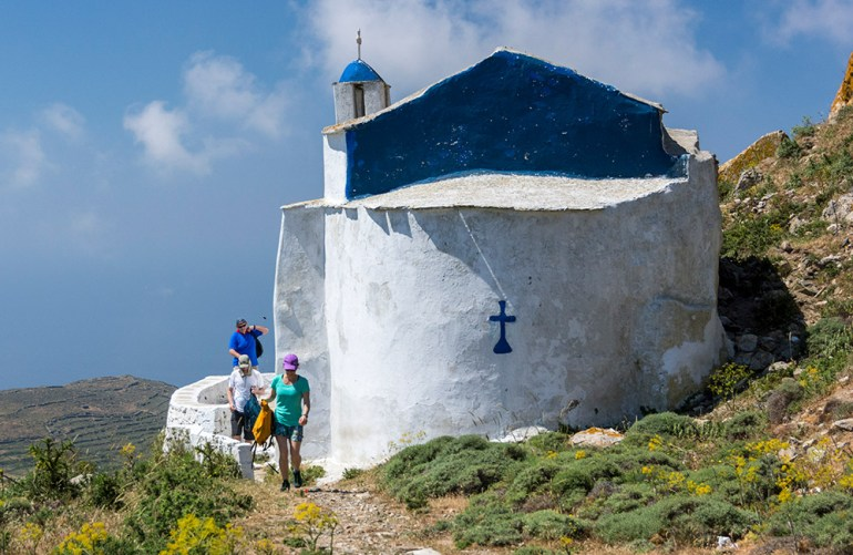 Hikers near a blue-domed church in Greece