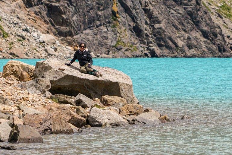 woman lounging rock at alfredo glacier in patagonia