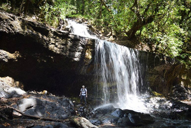 hiker near waterfall in tanzania