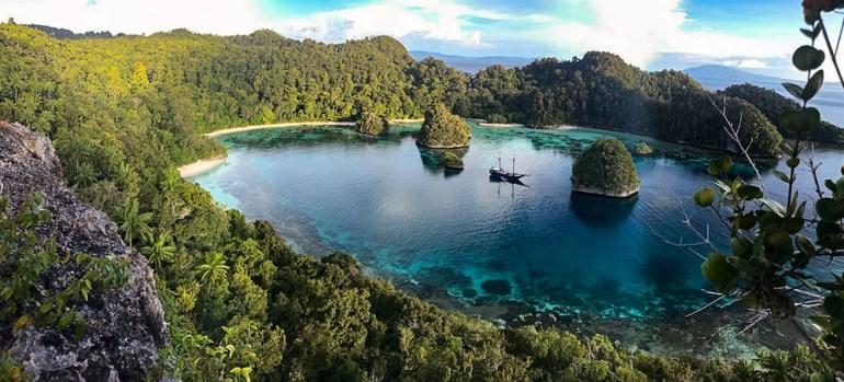 landscpae of bay and boat raja ampat