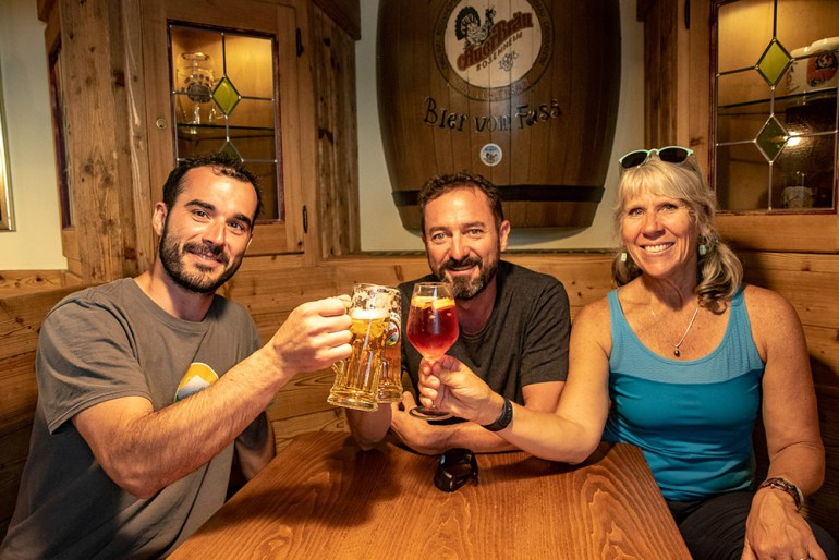 three people enjoying drinks in the Cortina Dolomites
