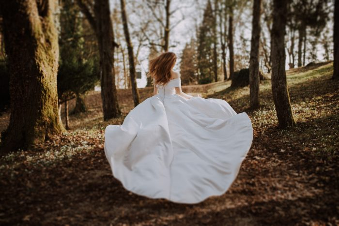 top pic of bride running through forrest