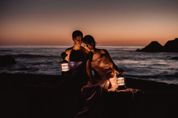 same sex couple on beach with lanterns April top pic