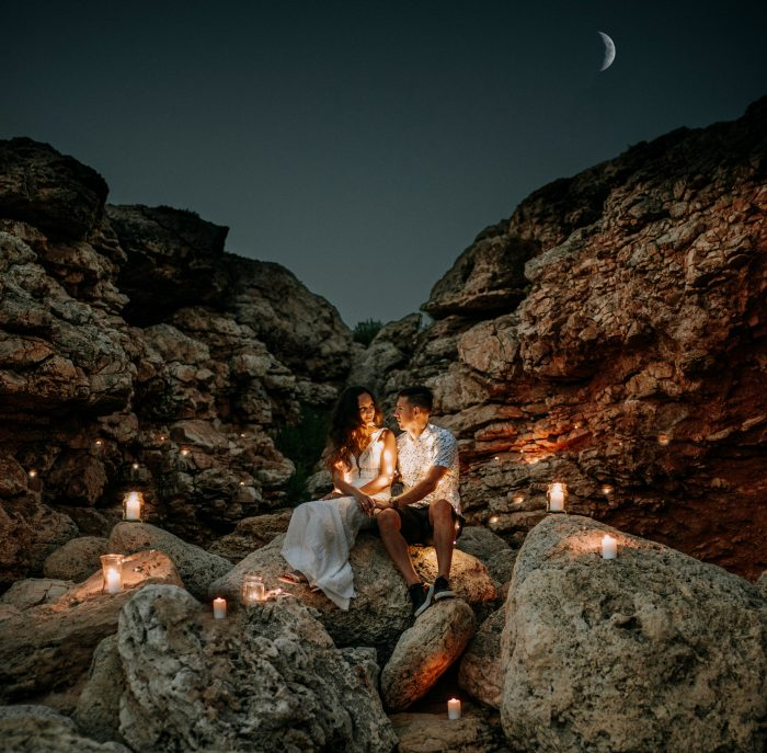 couple in rocky terrain surrounded by candles