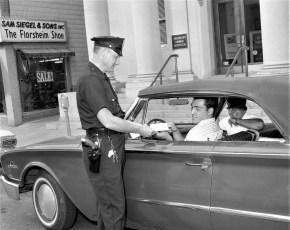 Patrolman Don Hanson selling Police Youth Day ticket to Joe Melino 1964