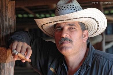 Fumeur de cigare dans un séchoir à tabac, Vinales, Cuba, Février 2014