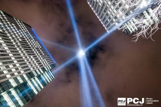 ビルの間にそびえる光の柱