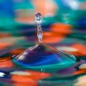 Macro of water drop falling in multicolored water