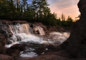 Adirondack waterfall at sunset framed by eroded rocks