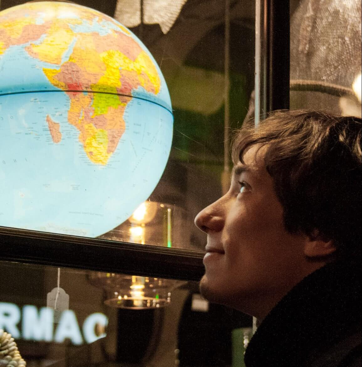 Photodyssee author Rico looking at a globe