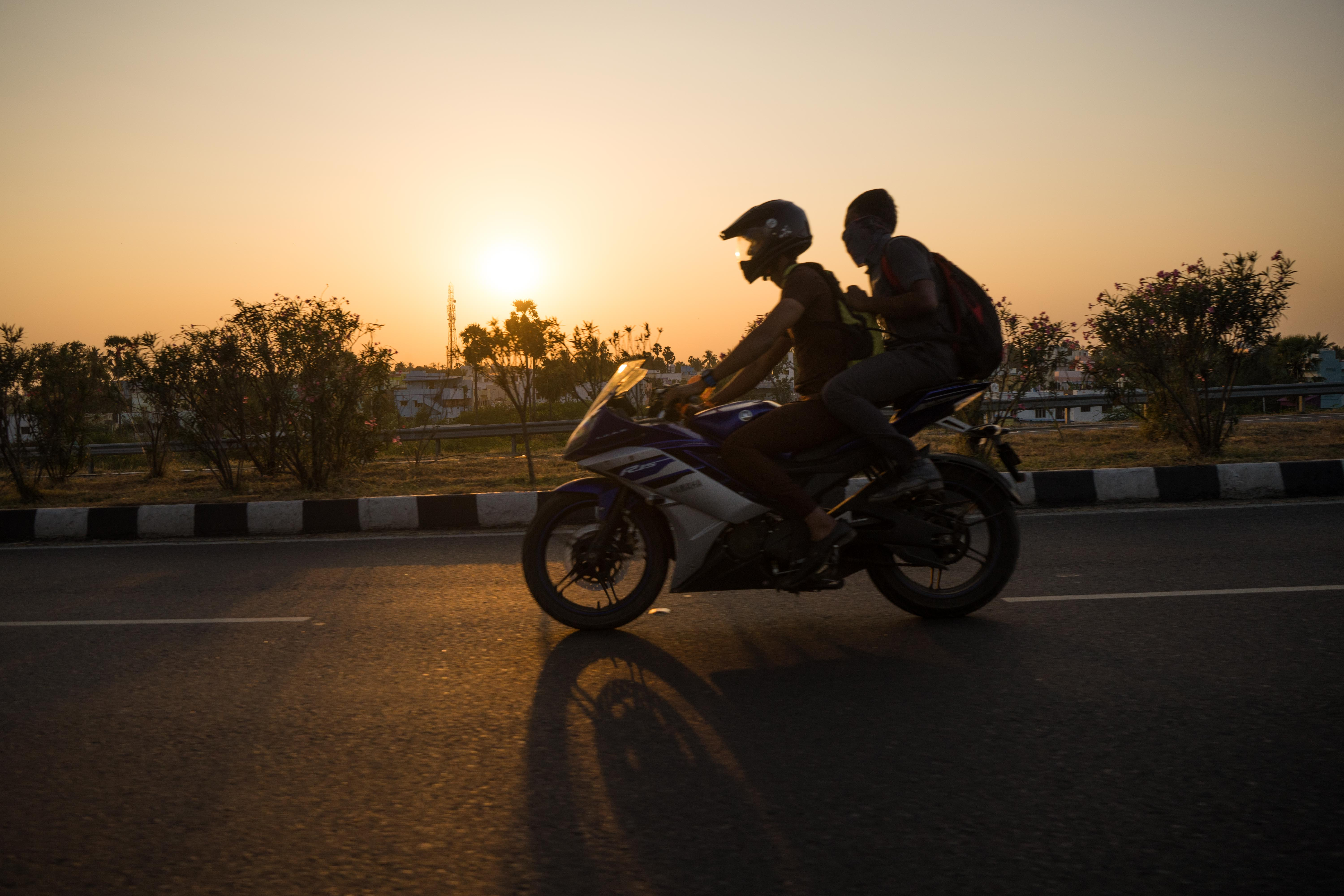 Motorbike passing in front of a sunset in India