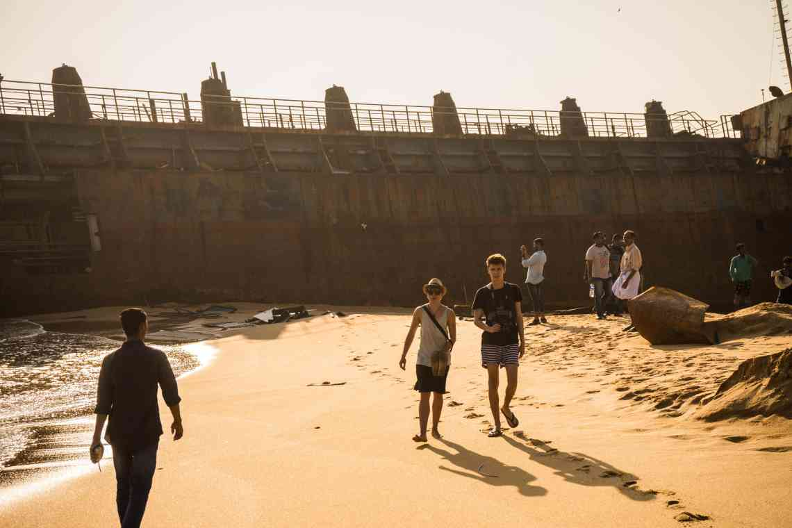 People walking in front of an old shipwreck washed ashore