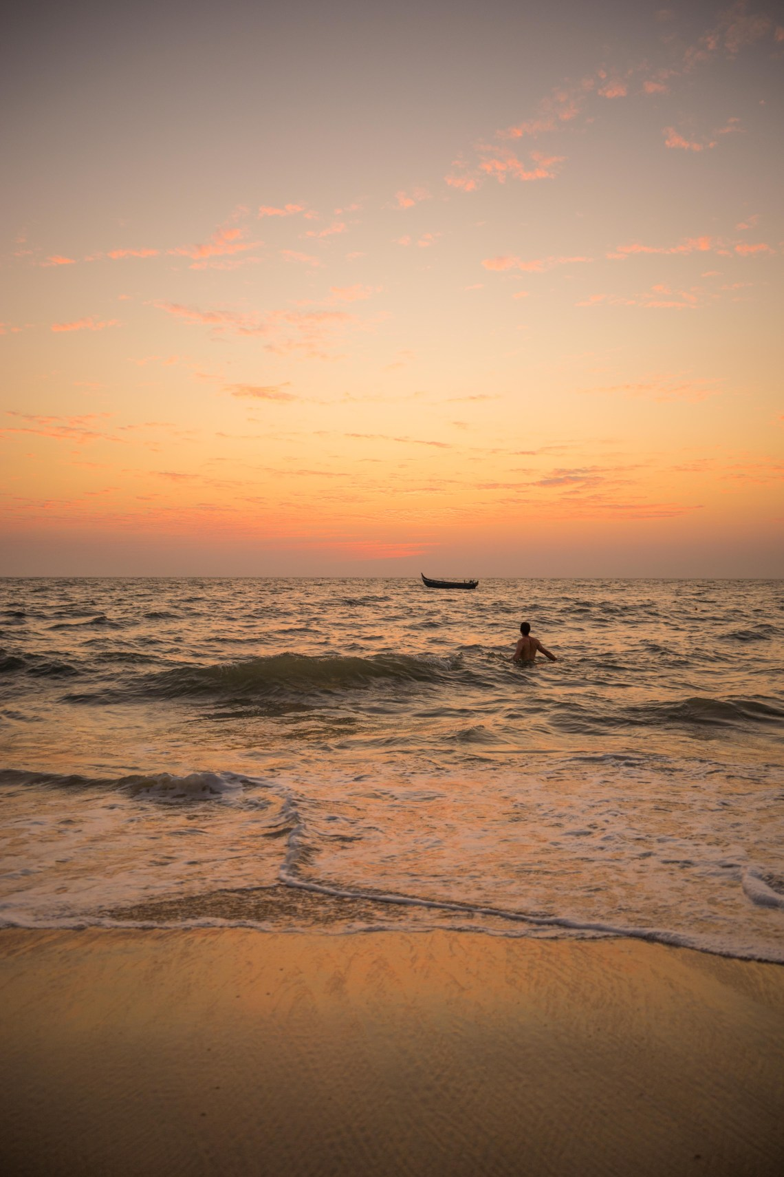 A person bathing in the sea shortly after sunset