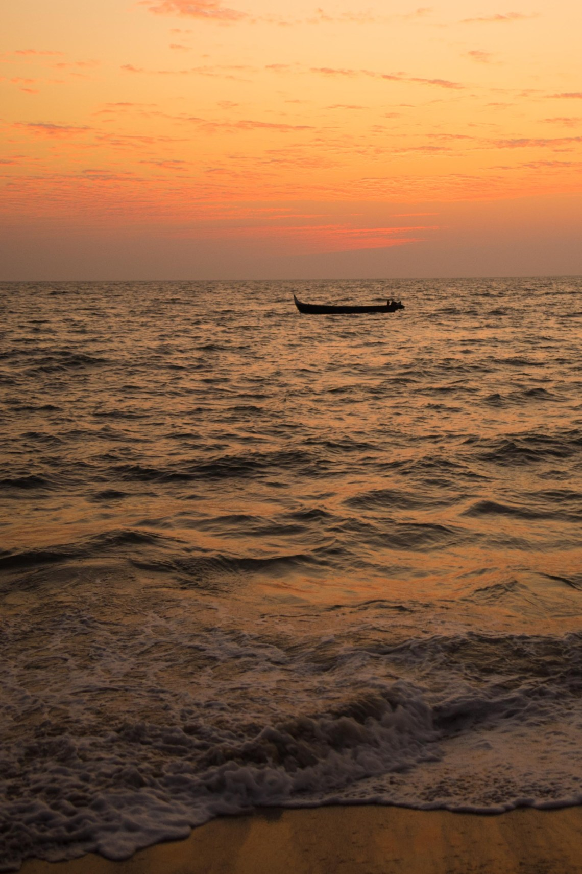 A boat floating in the orange tinted sea during sunset