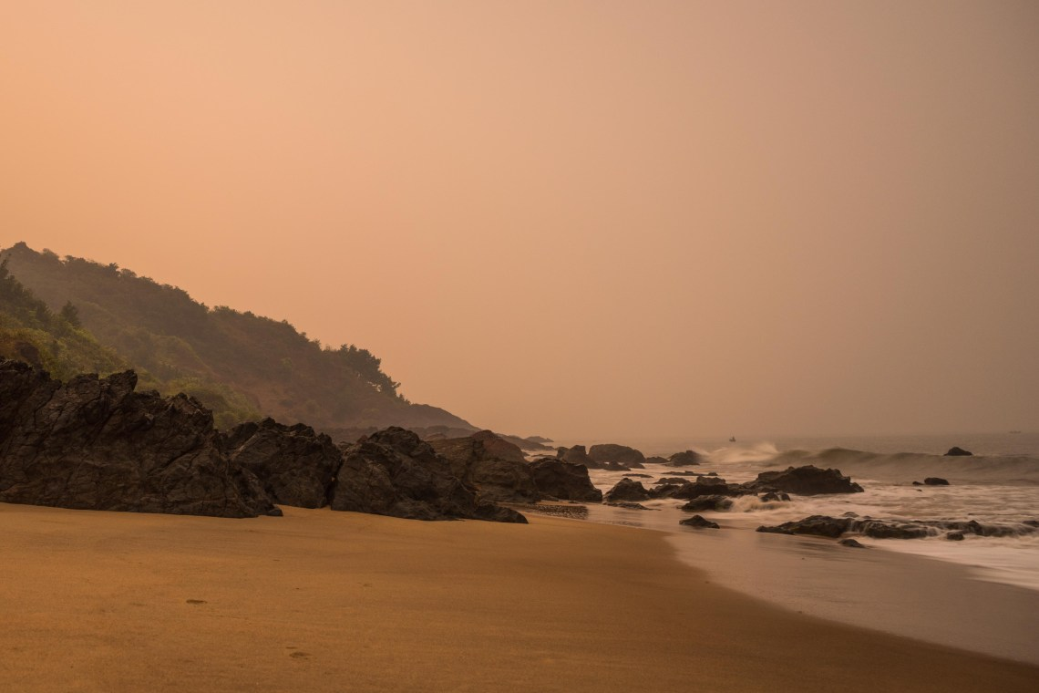 Boulders and sand touching the sea during evening hours at Kalwa beach in India