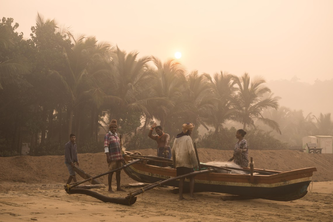 Some fishermen standing besides their boat on the shore in Kalwa