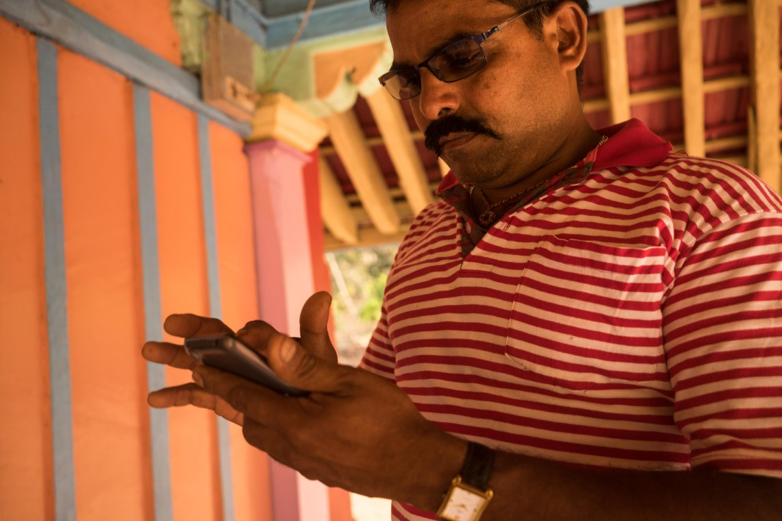 The major of Naravan checking his messages in front of the Hindu temple