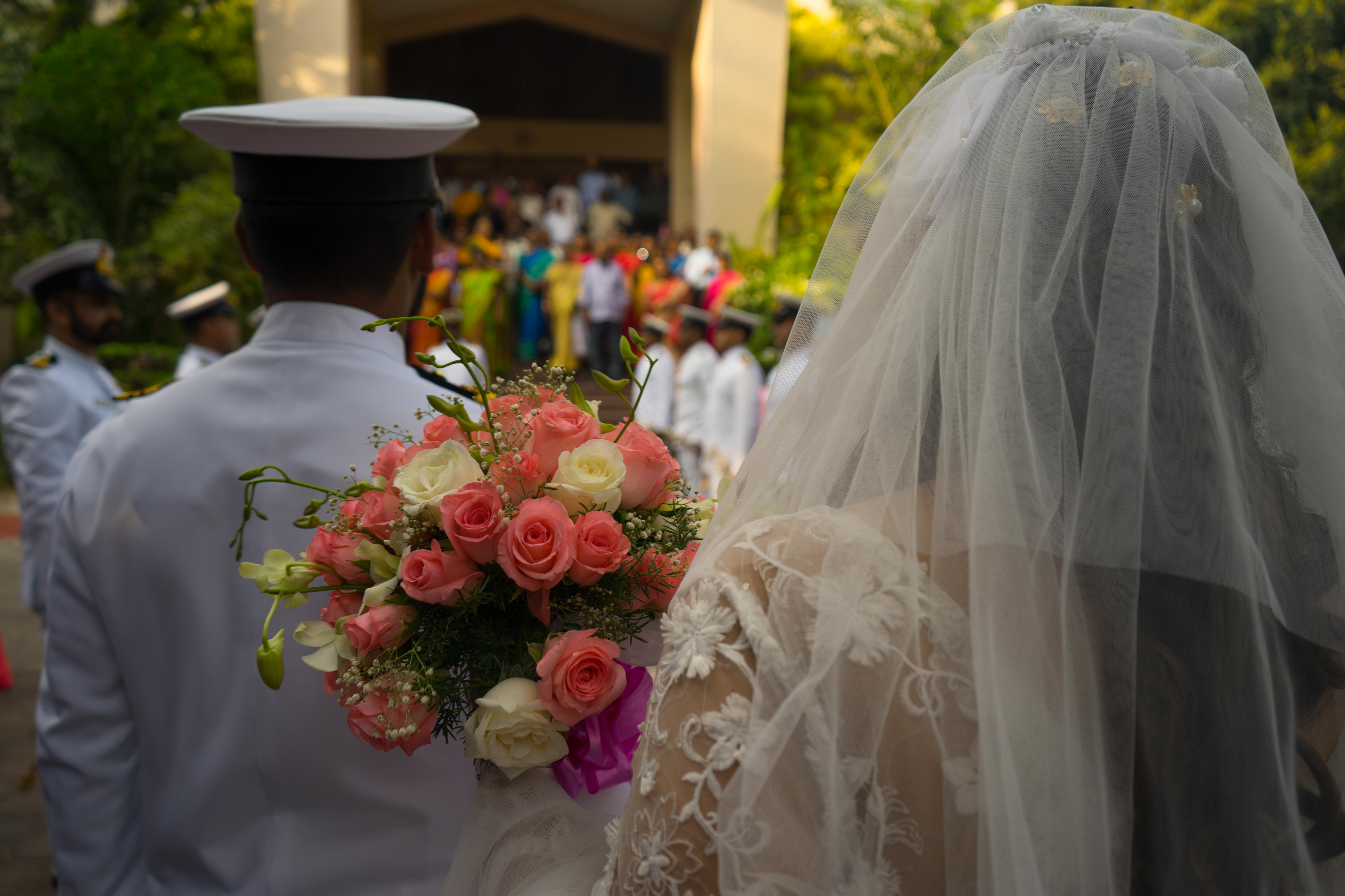 A bride walking with flowers in her hand behind the groom