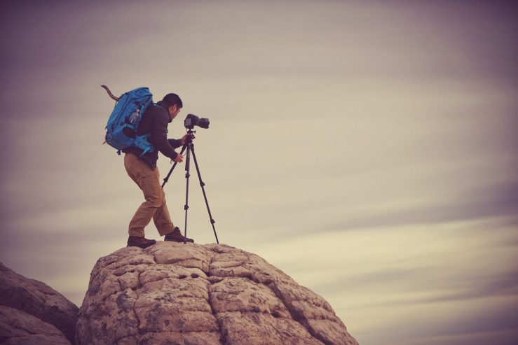 Photographer Moe Chen perched atop a mound of brain rock with his F-Stop Gear bag, camera and tripod