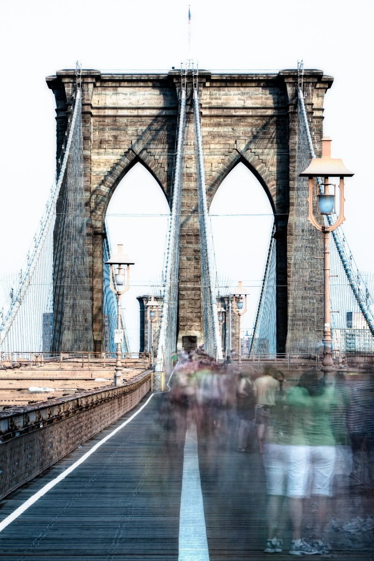A long exposure photo of the throngs of people crossing the Brooklyn Bridge